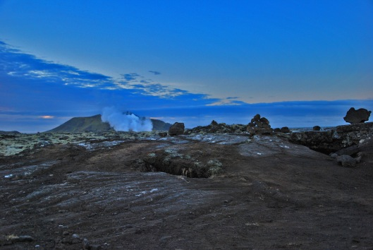 A collapsed lava tube flanked by steam from the Blue Lagoon.
