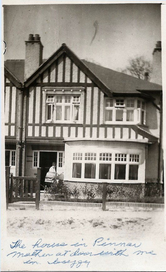 Norah with baby carriage in doorway of their house in Pinner district of northwest London. April 1914